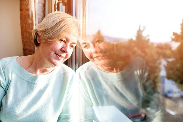 Frau in Quarantäne schaut aus dem Fenster